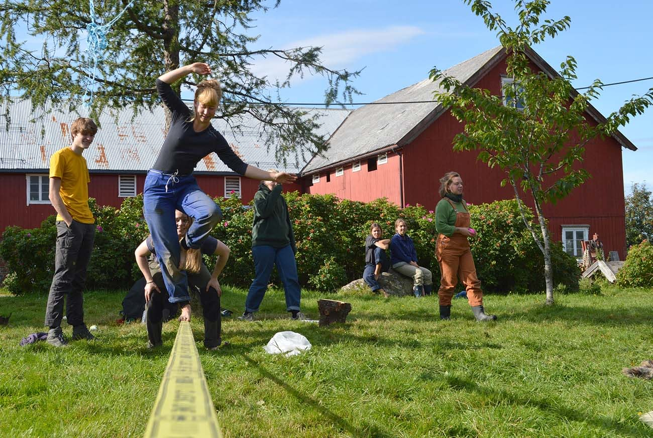 Students balancing on a slackline on an organic farm in Norway