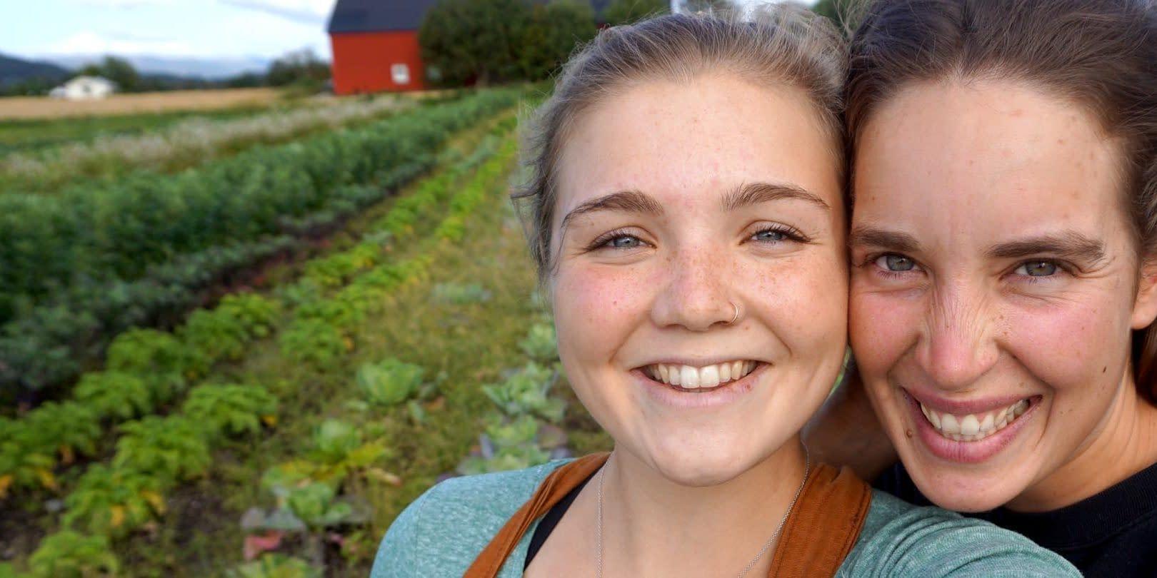 Glade jenter smiler til kameraet i en okologisk kjokkenhage