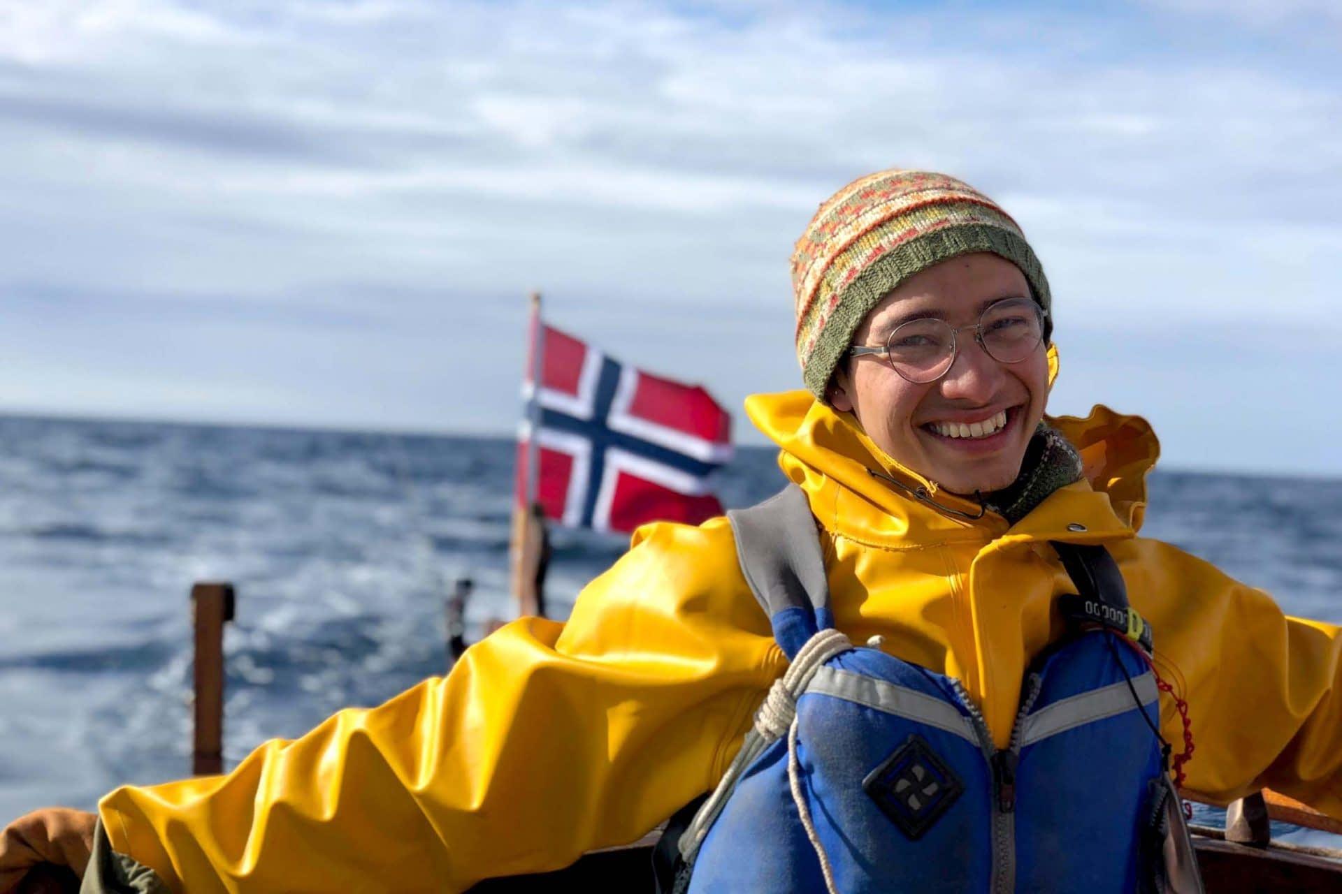 En glad elev med regntoy og flytevest styrer seilbaten i frisk vind. Det norske flagget i bakgrunnen.